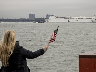 The U.S. Navy hospital ship Comfort is welcomed to New York City by Charlene Nickloan, waving a flag from the Matthew Buono war memorial in Staten Island, N.Y., on Monday.