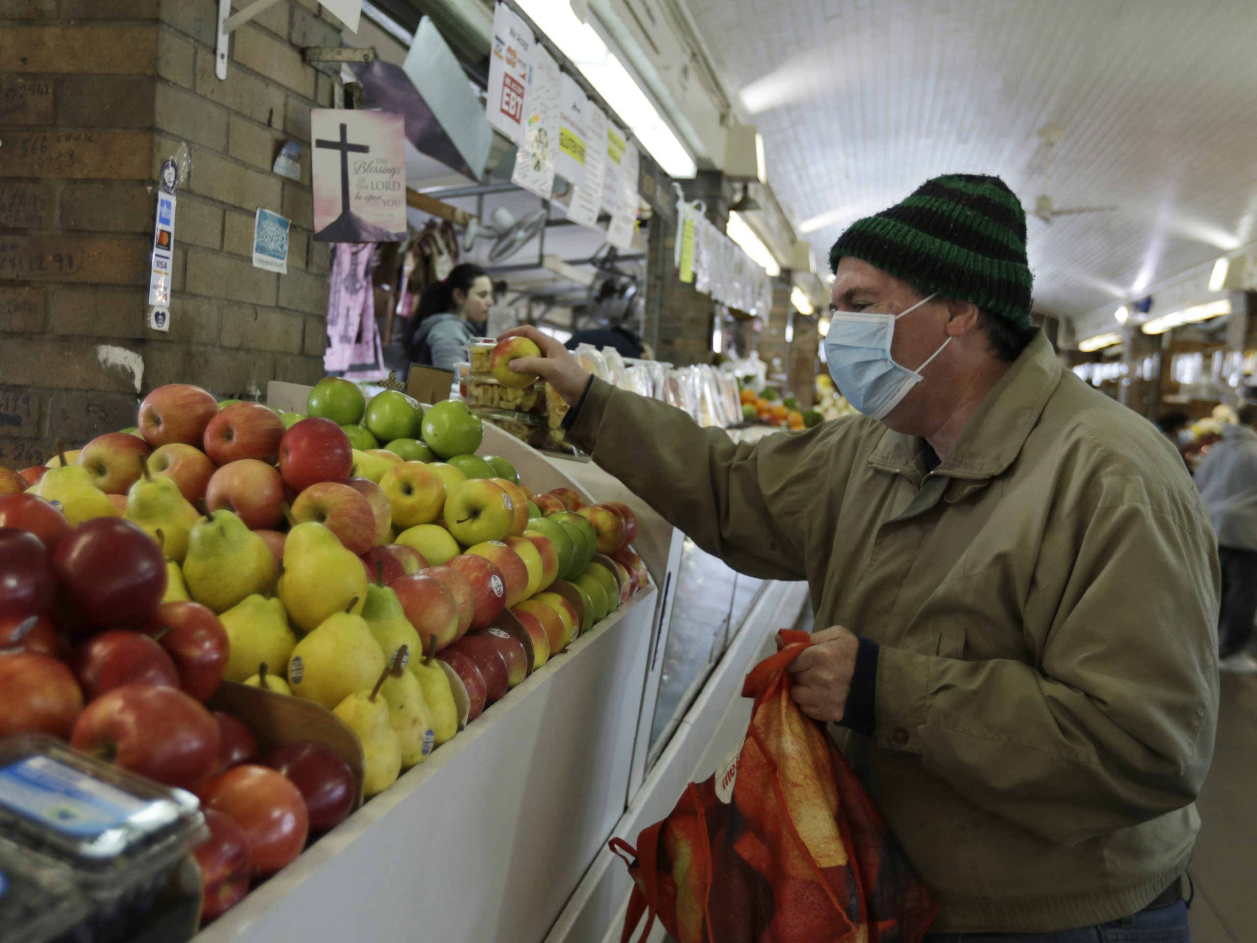 Rick Wittenmyer shops for groceries at the West Side Market, Friday, April 10, 2020, in Cleveland. There were fewer shoppers this year before the Easter holiday than in previous years due to the coronavirus.