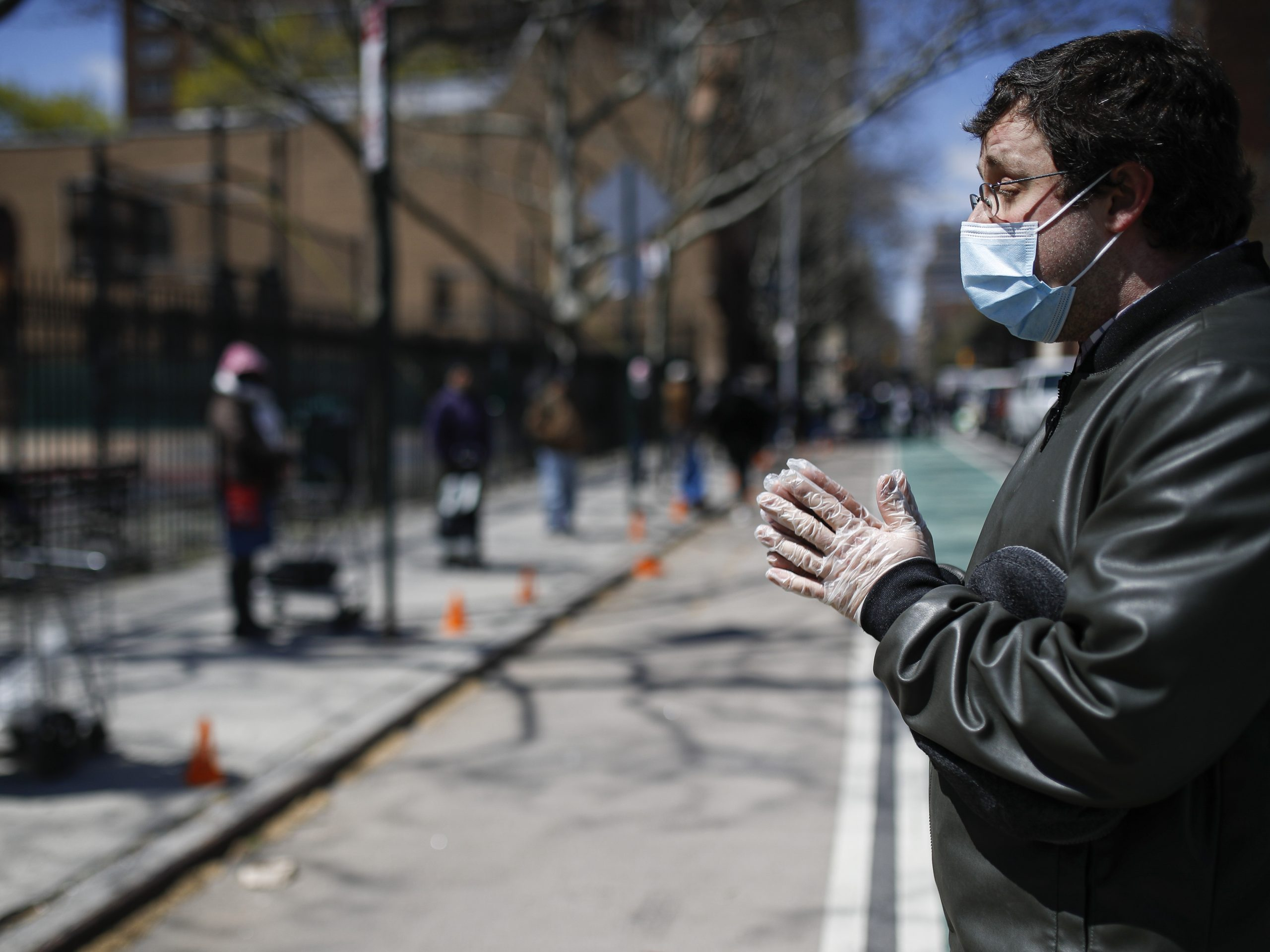 Christopher Love, general manager of the Covenant Mercy Mission, leads a prayer beside a line of visitors waiting for food donations at Manor Community Church on Saturday in New York. An additional 758 people died from the coronavirus over the past 24 hours, Gov. Andrew Cuomo said on Sunday.