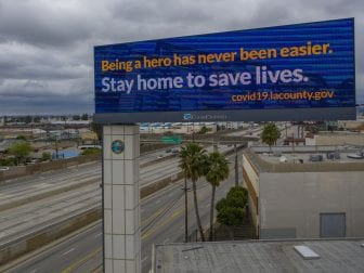 California Gov. Gavin Newsom and his counterparts in Oregon and Washington will coordinate their lifting of COVID-19 shutdowns, a move mirrored by New York and neighboring states in the East. Here, a sign along Interstate 5 in Commerce, Calif., tells people to stay home.