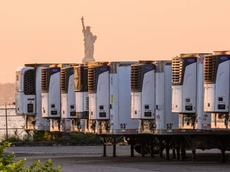 "The Statue of Liberty is seen behind refrigeration trucks that function as temporary morgues at New York City's South Brooklyn Marine Terminal. ""If you're driving by ... you might just assume that this was some sort of distribution hub,"" Time reporter W.J. Hennigan says. ""But they are each filled with up to 90 bodies apiece."