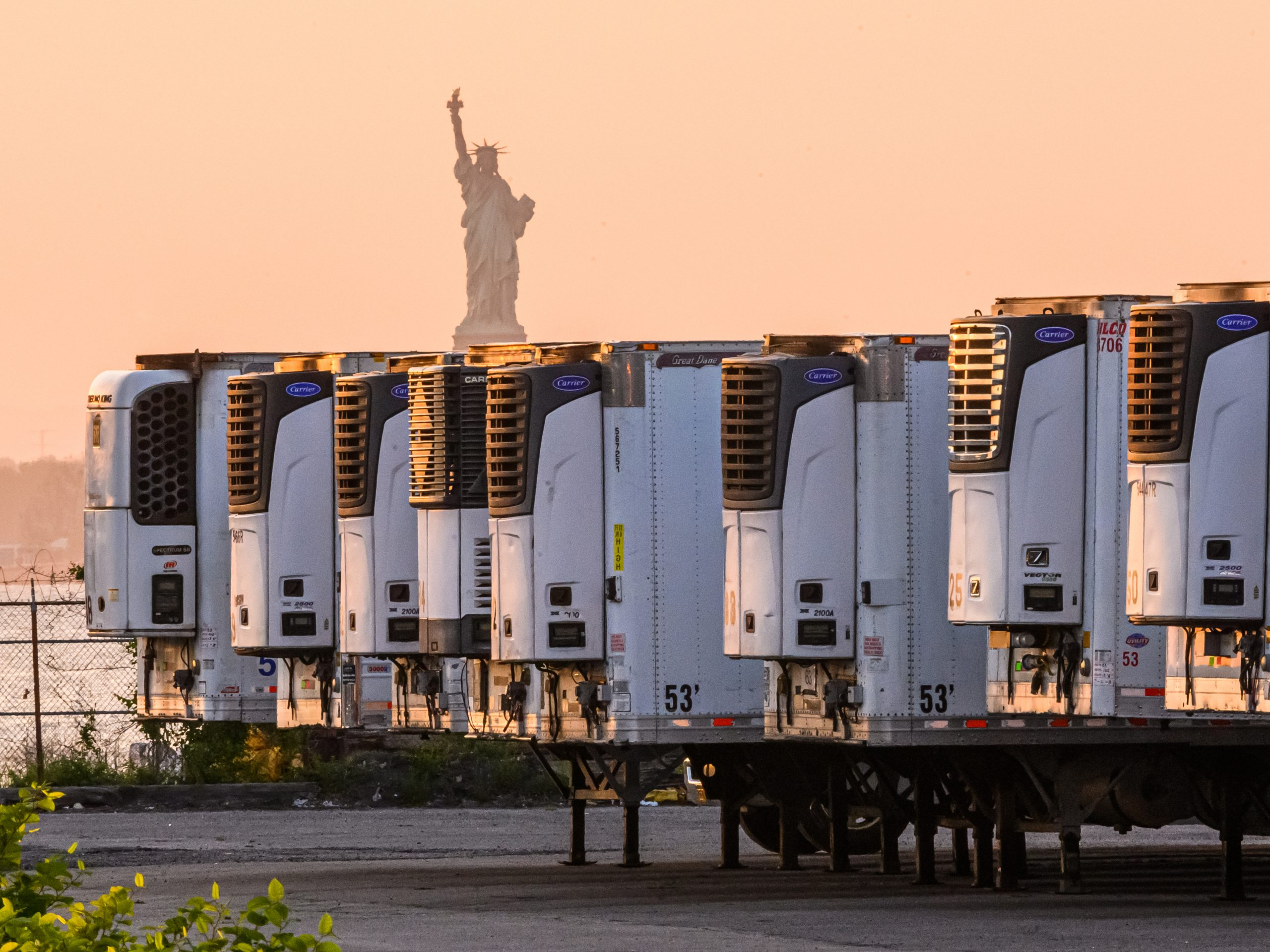 """The Statue of Liberty is seen behind refrigeration trucks that function as temporary morgues at New York City's South Brooklyn Marine Terminal. """"If you're driving by ... you might just assume that this was some sort of distribution hub,"""" Time reporter W.J. Hennigan says. """"But they are each filled with up to 90 bodies apiece."""