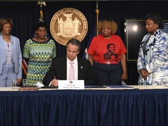 On June 12, New York Governor Andrew Cuomo (center) signs into law a package of police accountability measures that received new backing after the killing of George Floyd.