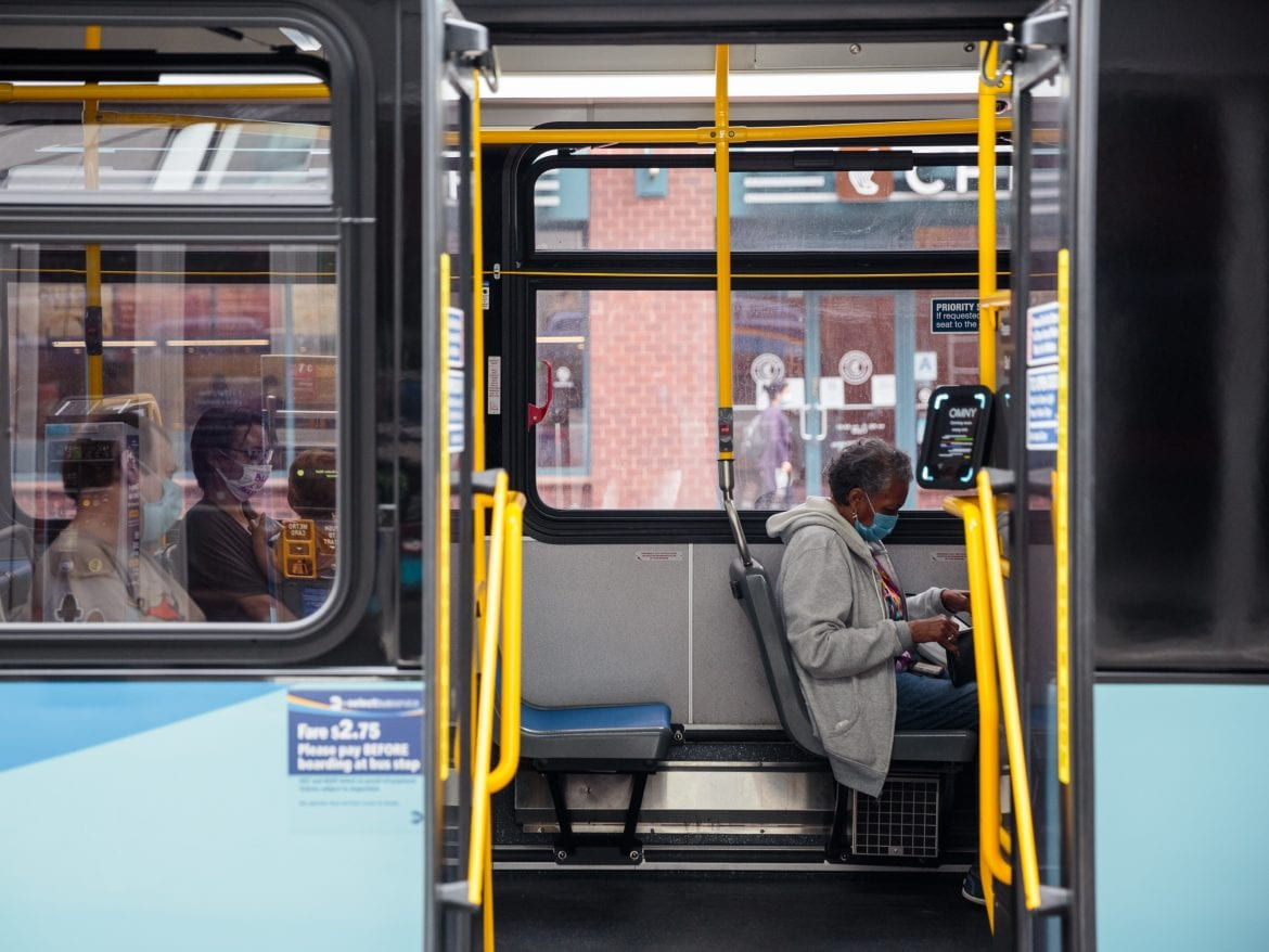 Passengers wearing protective masks sit inside a bus while waiting by Union Square in New York City.