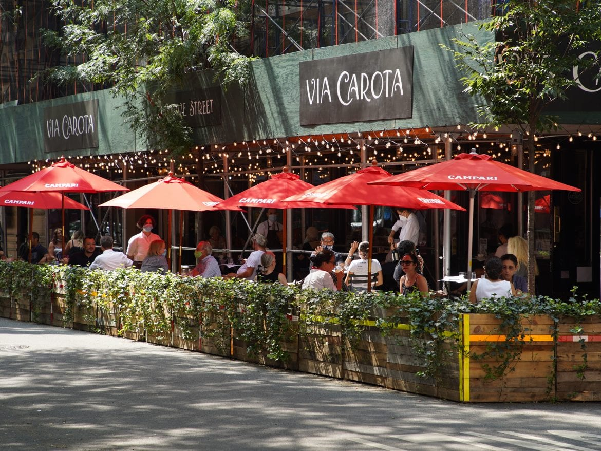 People dine under red umbrellas outside Via Carota restaurant in New York City's West Village. As the city continues to reopen, it is allowing restaurants to expand outdoors.