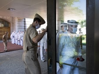 A Plebe Summer Detailer holds the door for a company of plebes as they enter a building on campus.