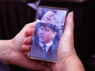 Priscilla Wass of Watertown, Mass., holds a picture of her high school classmate, FDNY Chief of Department Peter J. Ganci Jr., at a gathering outside Boston's Faneuil Hall during a memorial on Sept. 11, 2002.