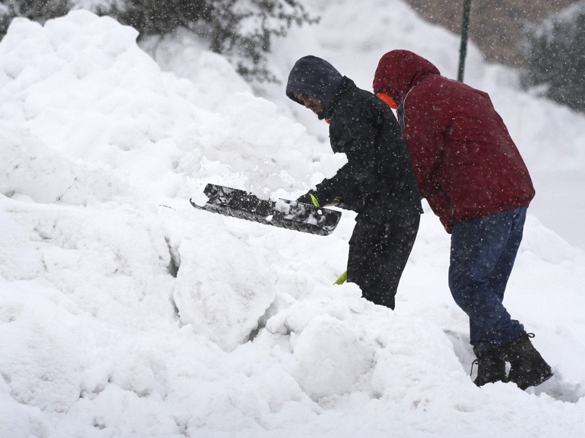 Residents of Wheeling, Ill, shovel snow in front of their house, Sunday, Jan. 31, 2021, in Wheeling, Ill. The winter storm may leave more than 1 foot of snow in the Chicago area.