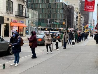 A line forms outside a COVID-19 testing clinic in Lower Manhattan. Long waits have created a business opportunity for line standers who used to queue up for others at Broadway shows and other major events.