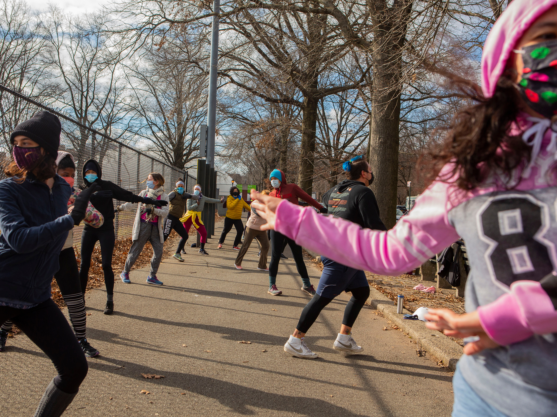Michael Aredes teaches a Zumba class outside Prospect Park in  Brooklyn. About 10 women bundled up to join the socially distant exercise class on a recent Saturday.