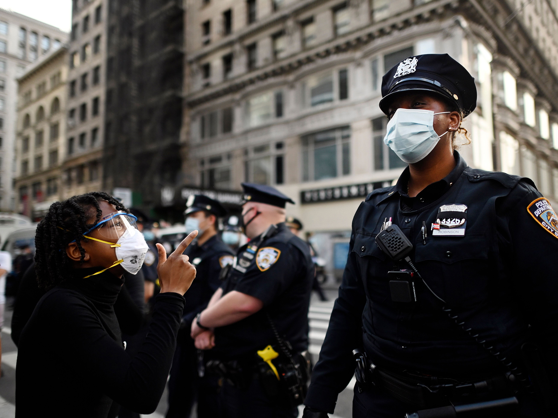 """Protestors shout in front of NYPD officers during a """"Black Lives Matter"""" demonstration last summer in New York City, in outrage over the death of a black man in Minnesota who died after a white policeman kneeled on his neck for several minutes."""