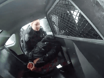 A frame from a Rochester Police Department body-camera video shows a girl in handcuffs in the back of a police cruiser.