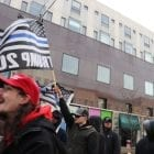 """A man in a """"Make America Great Again"""" hat in front of another holding a """"thin blue line"""" flag"""