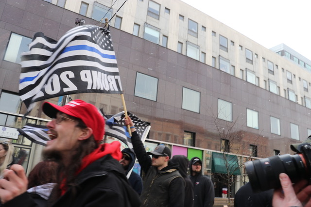 "A man in a ""Make America Great Again"" hat in front of another holding a ""thin blue line"" flag"