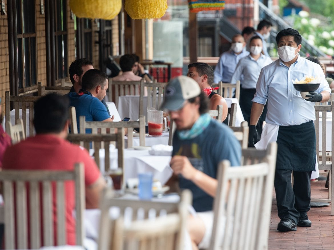 A waiter wearing a mask and gloves delivers food to a table to customers seated at an outdoor patio at a restaurant in Washington, D.C. in May.