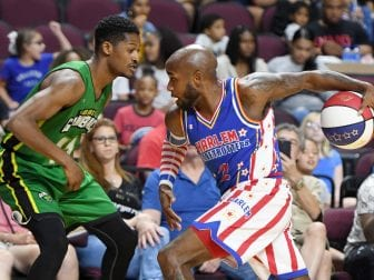 """Carlos """"Dizzy"""" English #2 of the Harlem Globetrotters drives against Shaquille Burrell #11 of the Washington Generals during their exhibition game at the Orleans Arena."""