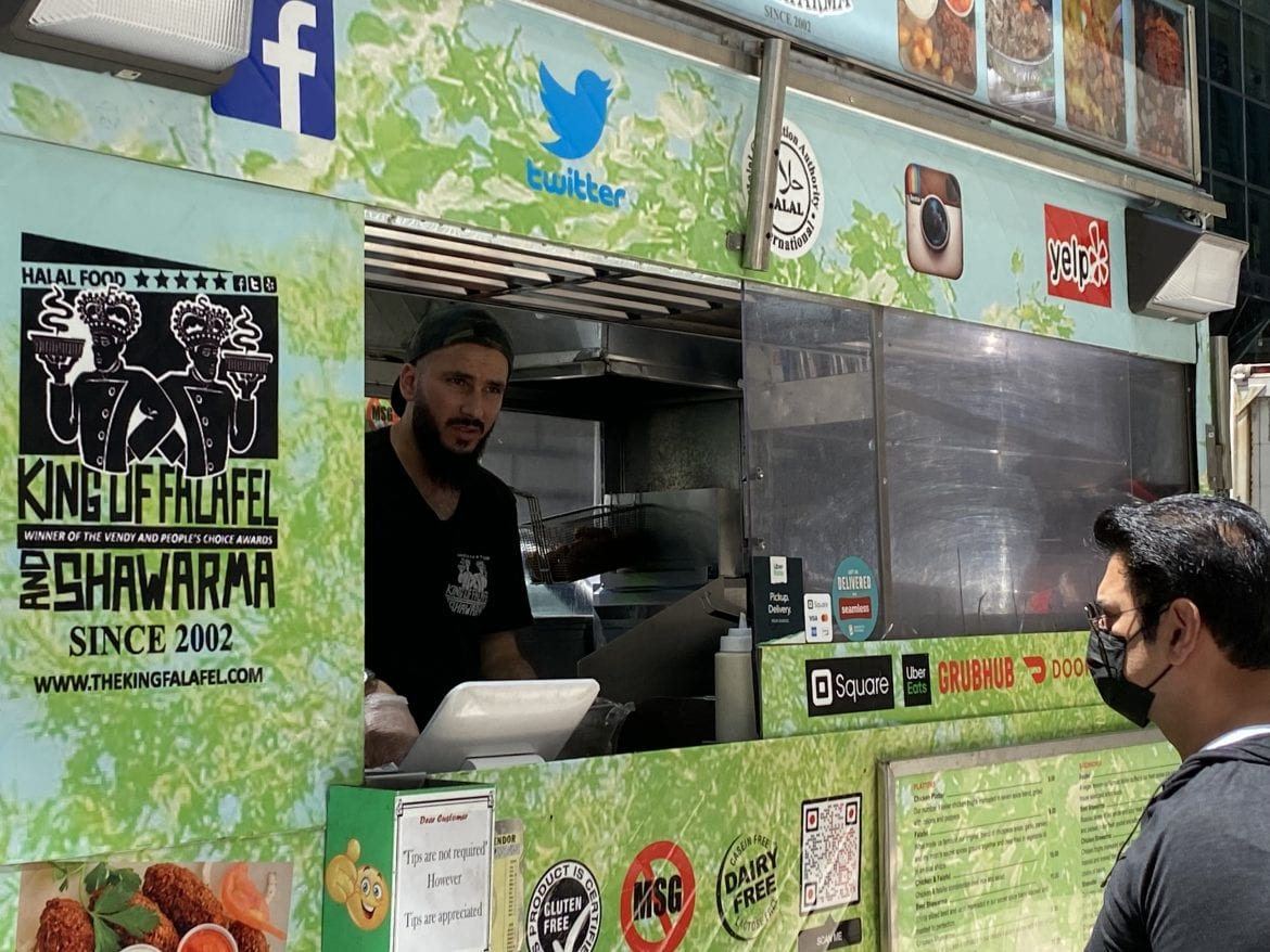 David Shadaha, who operates a cart called King of Falafel & Shawarma, takes an order from a customer in Midtown Manhattan, N.Y. Shadaha is back selling food after taking a job as a GrubHub deliveryman during the pandemic.